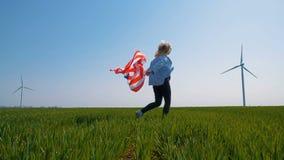 有一面旗子的美国本地人女孩在一个领域的一台巨型风车附近在慢动作 影视素材