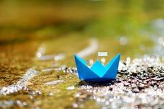 有一面白旗的蓝纸小船 免版税图库摄影