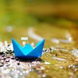 有一面白旗的蓝纸小船 免版税库存图片