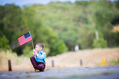 有一面美国国旗的一个年轻男孩,喜悦是美国人 免版税库存图片