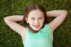 有一颗缺掉牙的一个女孩在她说谎在草 免版税库存照片