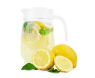 有一鲜美mojito的一个巨大的水罐从成熟柠檬,新鲜的绿色薄荷叶和鲜绿色的石灰,隔绝在白色背景 免版税库存照片