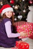 有一件大红色圣诞节礼物的快乐的女孩 库存照片