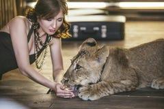 有一头小狮子的妇女,款待和浇灌它用水与 免版税图库摄影
