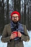 有一份热的饮料的聪明的胡子人在红色杯子在前面一个的冬天 免版税图库摄影