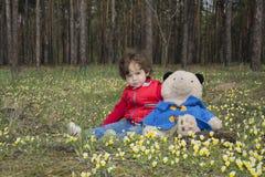 有一头熊的小女孩在森林坐花草甸 免版税图库摄影