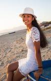 有一件白色礼服的美丽的年轻少年在太阳的海滩 免版税库存图片