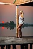 有一件白色衬衣的美丽的女孩在日落的码头 免版税库存照片