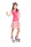 有一件盔甲的满意的女孩在溜冰鞋 免版税库存图片