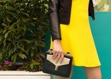 有一件短的黄色礼服的画象女孩,有一个黑提包的做购物 婴孩背景机体现有量一点在部分白色 欧洲市 库存照片