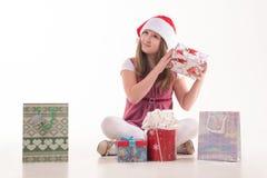 有一件礼物的女孩孩子在圣诞老人帽子 库存照片