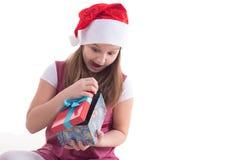 有一件礼物的女孩少年在圣诞老人帽子 免版税库存图片