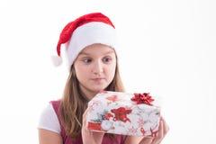有一件礼物的女孩少年在圣诞老人帽子 库存图片