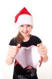有一件礼物的小女孩在圣诞老人帽子 免版税库存照片