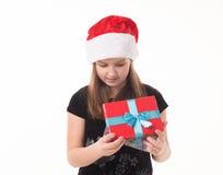 有一件礼物的小女孩在圣诞老人帽子 免版税库存图片