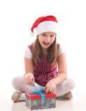 有一件礼物的小女孩在圣诞老人帽子 库存照片