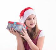 有一件礼物的小女孩在圣诞老人帽子 库存图片