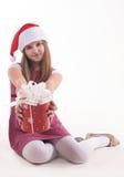 有一件礼物的小女孩在圣诞老人帽子 免版税图库摄影
