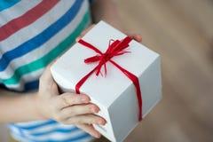 有一件礼物的箱子在孩子的手上 库存照片