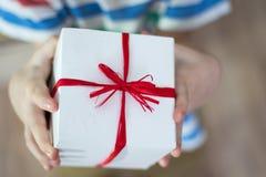 有一件礼物的箱子在孩子的手上 免版税图库摄影