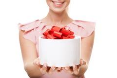 有一件礼物的年轻愉快的微笑的妇女在手上 在礼物的焦点 免版税库存图片