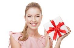 有一件礼物的年轻愉快的微笑的妇女在手上 查出 免版税库存图片