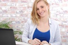 有一件蓝色毛线衣的美丽的白肤金发的女商人 免版税库存图片