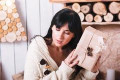 有一件被包裹的圣诞节礼物的体贴的女孩 免版税图库摄影