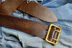 有一件铜扣和被撕毁的牛仔裤的布朗传送带 免版税库存照片