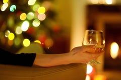 有一份饮料的妇女由在圣诞节的一个壁炉 免版税库存图片