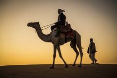 有一头骆驼的人在一片沙漠在苏丹 免版税库存照片