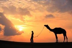 有一头骆驼的在日落,在贾伊斯附近的塔尔沙漠现出轮廓的人 免版税图库摄影