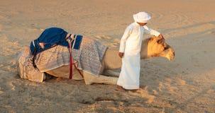 有一头骆驼的阿拉伯男孩在农场 图库摄影