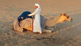 有一头骆驼的阿拉伯男孩在农场 库存图片