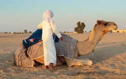 有一头骆驼的阿拉伯男孩在农场 免版税库存图片