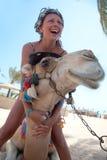 有一头骆驼的年轻美丽的妇女在海滩 库存图片