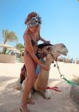 有一头骆驼的年轻美丽的妇女在海滩 免版税图库摄影