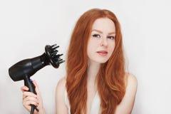有一hairdryer的年轻美丽的红发女孩在她的在白色背景的手上 免版税库存图片