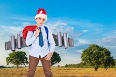 有一jetpack的年轻圣诞老人在他的后面举行礼物 库存照片