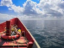 有一lifebuoy的红色木小船在海在一好日子,天空背景 免版税库存照片
