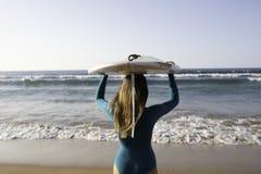 有一longboard的俏丽的海浪女孩在海滩 库存照片