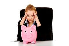 有一piggybank的担心的女商人在书桌后 库存图片