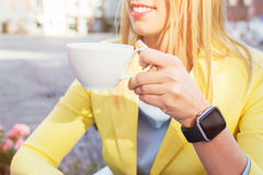 有一smartwatch的妇女在她的拿着一杯咖啡的腕子附近 免版税库存图片