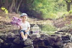 有丁香和鸟笼的男孩在池塘 免版税库存照片
