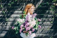 有丁香淡紫色花束的女孩在庭院里 撕毁丁香的女孩在庭院里 免版税库存照片
