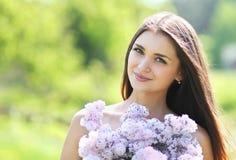 有丁香花束的可爱的逗人喜爱的微笑的女孩  免版税库存图片