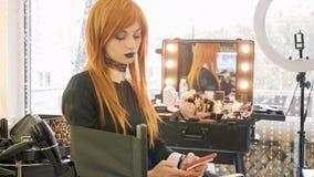 有万圣夜构成的年轻美丽的女孩使用在美容院的巧妙的电话 库存照片