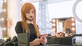 有万圣夜构成的年轻美丽的女孩使用在美容院的巧妙的电话 免版税库存照片