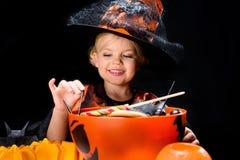 有万圣夜甜点的小巫婆 库存图片