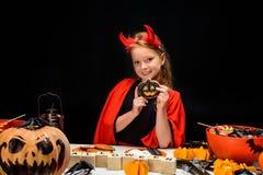 有万圣夜甜点的小恶魔 免版税库存照片